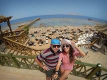Hombre y mujer en gafas de sol en el fondo de la playa Imagenes de archivo