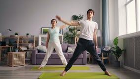 Hombre y mujer en la familia de la ropa de deportes que hace yoga en el apartamento moderno almacen de metraje de vídeo