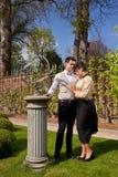 Hombre y mujer en la ropa de Vicorian, el pilar y el reloj de sol en el parque Imágenes de archivo libres de regalías