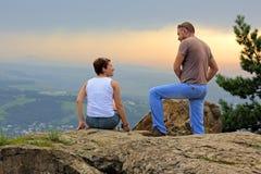 Hombre y mujer en la tapa de la montaña en la puesta del sol fotografía de archivo libre de regalías