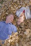Hombre y mujer en las hojas que miran el eachother Fotos de archivo