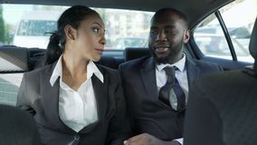Hombre y mujer en los trajes de negocios que se sientan en el asiento trasero del coche, ligando, afecto almacen de video