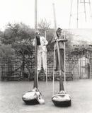 Hombre y mujer en los zancos que detienen a los clubs de golf gigantes imagen de archivo