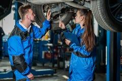 Hombre y mujer en mecánicos de automóviles Foto de archivo libre de regalías
