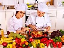 Hombre y mujer en sombrero del cocinero que cocinan el pollo Fotografía de archivo libre de regalías