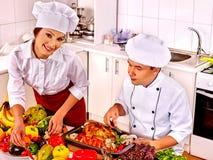 Hombre y mujer en sombrero del cocinero que cocinan el pollo Imagen de archivo