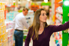 Hombre y mujer en supermercado con el carro de compras Foto de archivo libre de regalías