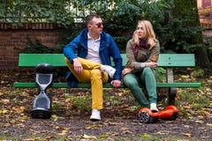 Hombre y mujer en un banco con hoverboards Imagen de archivo libre de regalías
