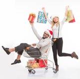 Hombre y mujer felices con el carro de la compra Fotos de archivo