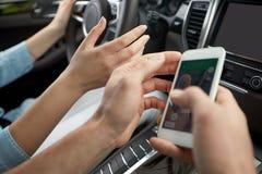 Hombre y mujer felices con el smartphone que conduce en coche Fotografía de archivo