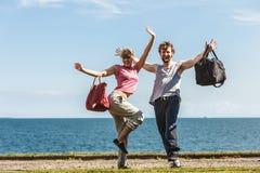 Hombre y mujer felices de los pares con los bolsos del deporte Fotografía de archivo libre de regalías