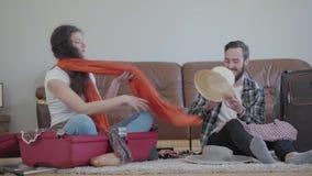 Hombre y mujer felices del retrato en el piso en casa delante del sof? de cuero, embalando una maleta antes de viaje La esposa almacen de video