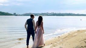 Hombre y mujer, gente joven, pareja adulta casada feliz que se divierte y que juega en la orilla, playa metrajes