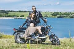 Hombre y mujer hermosos de los pares en una motocicleta en un fondo o foto de archivo libre de regalías