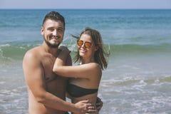 Hombre y mujer hermosos jovenes felices de los pares en la playa en el b Foto de archivo libre de regalías