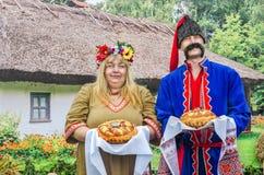 Hombre y mujer hospitalarios en los trajes nacionales ucranianos Fotos de archivo libres de regalías