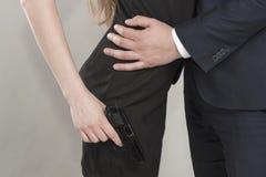 Hombre y mujer irreconocibles caucásicos en negro con un arma Imagen de archivo libre de regalías