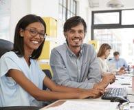 Hombre y mujer joven en la oficina abierta del plan que mira al ½ del ¿del cameraï Imagen de archivo