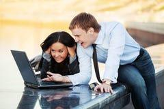 Hombre y mujer jovenes de negocios que usa el ordenador portátil Imagen de archivo libre de regalías
