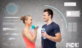 Hombre y mujer juguetones con pesa de gimnasia y agua Fotos de archivo libres de regalías