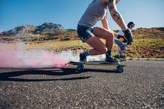 Hombre y mujer longboarding abajo del camino Foto de archivo libre de regalías