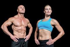 Hombre y mujer musculares con la mano en cadera Imagen de archivo libre de regalías
