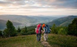 Hombre y mujer pelirroja en el camino en las montañas Foto de archivo libre de regalías