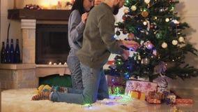 Hombre y mujer que adornan el árbol de navidad en casa Los pares felices se preparan para la fiesta de Navidad Concepto de ocio e metrajes
