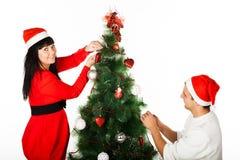 Hombre y mujer que adornan el ?rbol de navidad Fotos de archivo libres de regalías