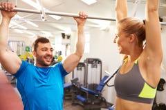 Hombre y mujer que alcanzan hasta barras de mono en un gimnasio Foto de archivo libre de regalías