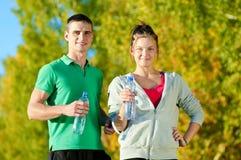 Hombre y mujer que beben de la botella Imágenes de archivo libres de regalías