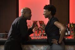 Hombre y mujer que beben en la barra Imagenes de archivo