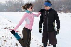 Hombre y mujer que calientan antes de exterior corriente en nieve Foto de archivo