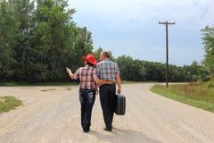 Hombre y mujer que caminan abajo del camino de tierra que lleva una maleta Imagen de archivo libre de regalías