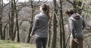 Hombre y mujer que caminan y que caminan en el bosque de maderas de abedul que sigue detrás Junte a la gente en viaje al aire lib almacen de video