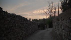 Hombre y mujer que caminan en la calle durante puesta del sol En las montañas almacen de metraje de vídeo