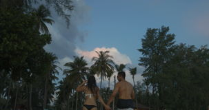 Hombre y mujer que caminan en la playa que lleva a cabo las manos en pares del crepúsculo juntas de turistas en la playa metrajes