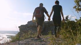 Hombre y mujer que caminan a lo largo de una trayectoria de la montaña Calzado turístico almacen de video