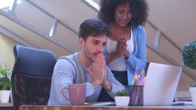 Hombre y mujer que celebran éxito en línea en la oficina almacen de video