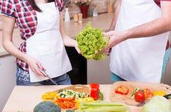 Hombre y mujer que cocinan junto en cocina Imágenes de archivo libres de regalías