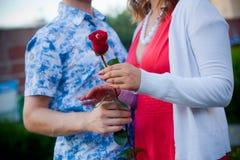 Hombre y mujer que colocan y que llevan a cabo un abarcamiento de la flor Fotos de archivo libres de regalías