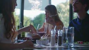 Hombre y mujer que comen y que hablan Ensalada de cuatro personas caucásicas de los amigos, filete de la carne y almuerzo italian metrajes