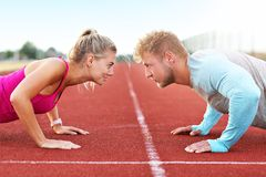 Hombre y mujer que compiten con en pista al aire libre imagen de archivo libre de regalías