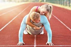 Hombre y mujer que compiten con en pista al aire libre foto de archivo