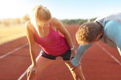Hombre y mujer que compiten con en pista al aire libre foto de archivo libre de regalías