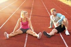 Hombre y mujer que compiten con en pista al aire libre fotografía de archivo