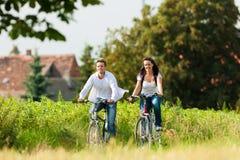 Hombre y mujer que completan un ciclo en verano Foto de archivo