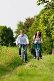 Hombre y mujer que completan un ciclo en verano Fotos de archivo