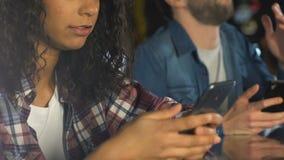 Hombre y mujer que comprueban la combinación en smartphones, lotería de observación del ganador almacen de video