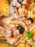 Hombre y mujer que consiguen masaje herbario de la bola en balneario. Foto de archivo
